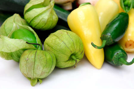 Yellow and green chili peppers with fresh tomatillos, ingredients for salsa on a white background. Reklamní fotografie