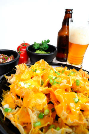 Plate of cheese nachos with sides of guacamole and salsa with an ice cold bottled beer poured in a glass photo