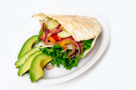 Pita bread sandwich with lettuce, swiss cheese, grilled onions and bell pepper, tomatoes, cucumber abd Avacado on a white plate