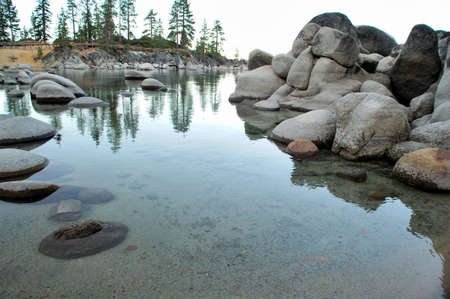 Small bay at Lake Tahoe with rounded granite boulders in the crystal clear water photo