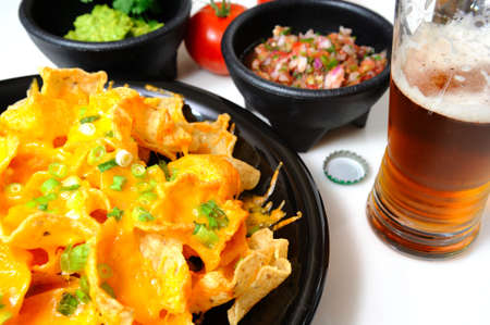 bottled beer: Cheese nachos with sides of guacamole and salsa with an ice cold bottled beer poured in a glass