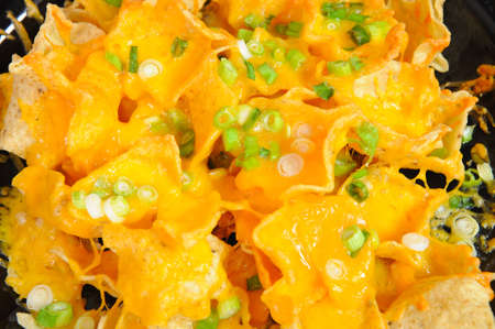 Plate of cheese nachos topped with thin sliced green onion Archivio Fotografico