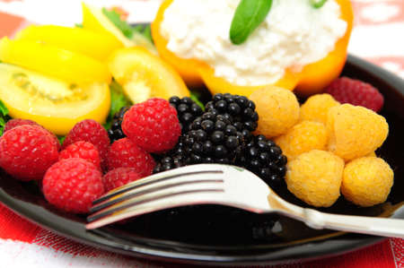 lo-cal salad made with red and golden raspberries, blackberries, yellow heirloom tomatoes with an orange bell pepper filled with cottage cheese topped with fresh basil