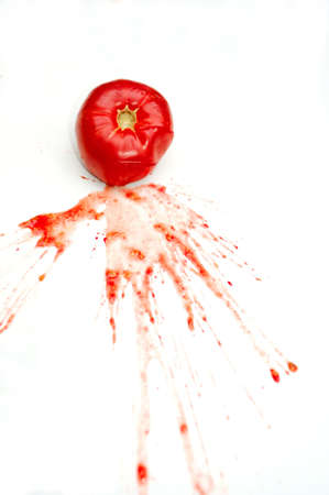 A single bright red tomato splattered on a white background with juice and seeds spread across the isolation Standard-Bild