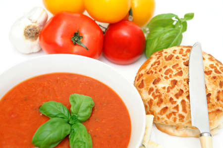 Bowl of tomato soup with crackers and a roll with  fresh tomatoes isolated on a white background photo