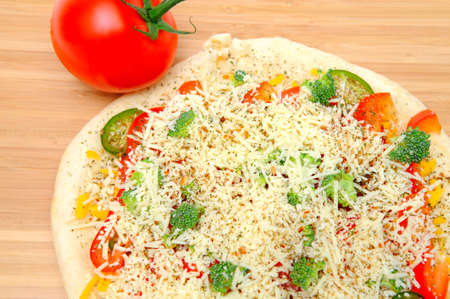 A veggie pizza ready to go into the oven topped with sharp cheddar and asiago cheese, fresh tomatoes, red bell pepper, mild jalapeno chilie, broccoli and dried herbs photo