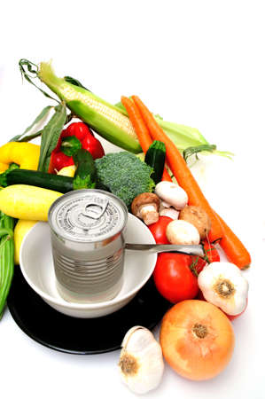 Vegetables for vegetable soup including carrot, bell pepper, broccoli, mushroom, squash, garlic, tomatoes or a can of store bought canned soup served in a white bowl on a black saucer