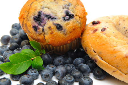 Fresh blueberries surround a single blueberry muffin and a bagel on a light background