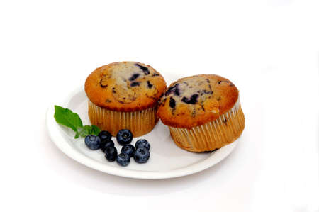 Blueberry muffins on a white plate with fresh berries on the side