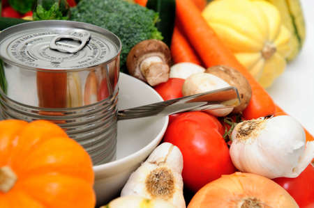 Vegetables for vegetable soup including carrot, bell pepper, broccoli, mushroom, squash, garlic, tomatoes or a can of store bought canned soup served in a white bowl