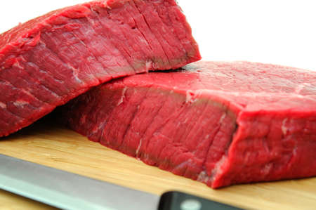 A large uncooked steak on a cutting board with butcher knife on a white background