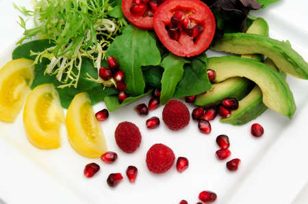 heirloom: Colorful salad with different types of greens, avocado, roma and yellow heirloom tomatoes, raspberries and pomegranate seeds Stock Photo