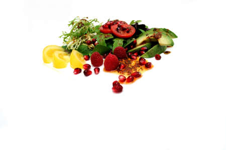 Salad ingredients isolated on a white background with red roma and yellow heirloom tomatoes, avocado slices, spinach leaf, pomegranate seeds, Raspberries topped with Olive oil and Raspberry vinaigrette dressing
