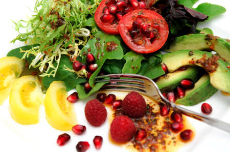 Salad on a white plate  with red roma and yellow heirloom tomatoes, avocado slices, spinach leaf, pomegranate seeds, Raspberries topped with Olive oil and Raspberry vinaigrette dressing Archivio Fotografico