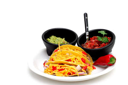Three hard shell tacos on a white plate with sides of tomato and chili salsa and fresh guacamole isolated on a light colored background Standard-Bild