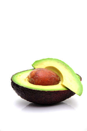 Avocado cut in half exposing the single seed and the various shades of green in the fruit Archivio Fotografico