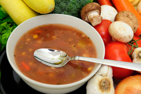 Bowl of veggie soup with a spoon surrouned by assorted fresh vegetables