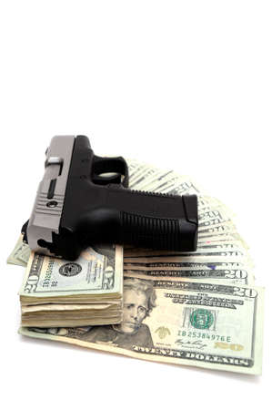 A silver and black handgun on top of a stack of United States twenty dollar bills on a white background. Archivio Fotografico