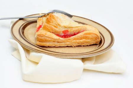 A sweet Cherry Turnover with course ground sugar on top served on an oval brown colored saucer with a light colored cloth napkin under the plate Фото со стока