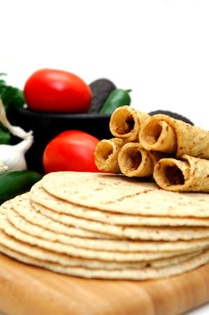Taquitos with other natural ingredients including homemade tortillas, avocados, tomatoes, small sweet onions and jalapeno chilies Archivio Fotografico