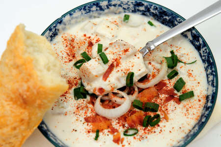 chowder: Hot bowl of New England Clam Chowder with crumbled bacon, green and white onion rings in a blue and white bowl