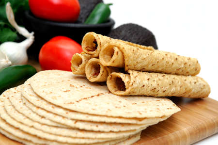 Taquitos with other natural ingredients including homemade tortillas, avocados, tomatoes, small sweet onions and jalapeno chilies photo