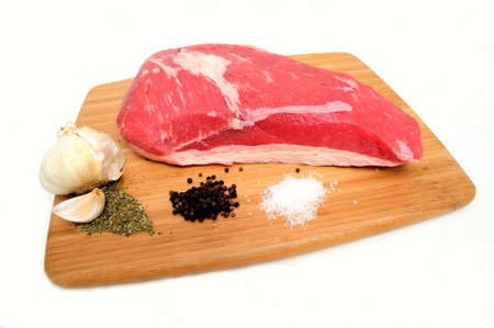 Fresh raw tri-tip roast with fat marbled through the meat ready to roast or barbeque with sea salt, black peppercorns, herbs and garlic cloves