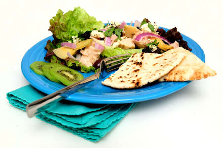 Tuna salad on a bed of Red Leaf Lettuce with Artichoke hearts, Kalamata olives, red onions and Feta Cheese, Kiwi slices and pita bread served on a turquoise colored plate Stock Photo - 6412394