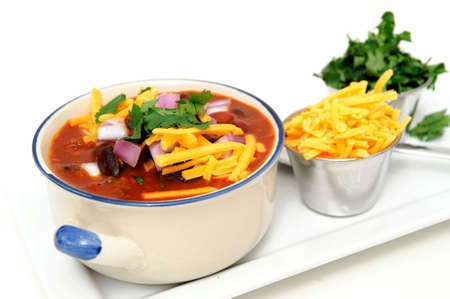 Chili and beans in a ceramic bowl with onion, cilantro and cheddar cheese sprinkled on with with sides of each in stainless steel condiment cups.