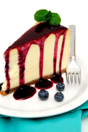 Plain Cheesecake with a Blueberry sauce poured over the top with fresh berries on the plate next to the cake and topped with a mint leaf.