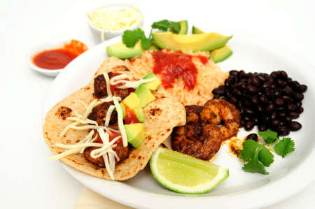 Shrimp cooked in Jamaican spices for tacos with black beans and Spanish rice, lime cilantro, cheese and hot sauce. Archivio Fotografico