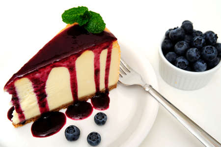 cheesecake: Plain Cheesecake with a Blueberry sauce poured over the top with fresh berries on the plate next to the cake and topped with a mint leaf.