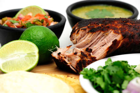 Pork roast cooked to make Mexican carnitas with fresh tortilla's' chunky tomato salsa and salsa verde and sliced limes Archivio Fotografico