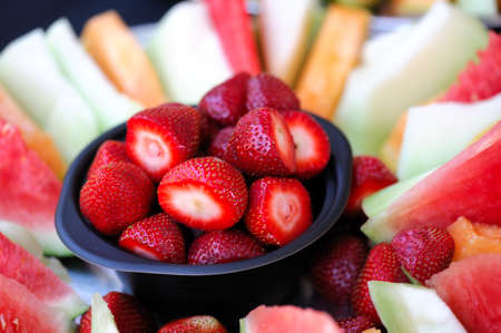 A bowl of cleaned strawberries surrounded by slices of watermelon cantaloupe and honeydew melon Stock fotó