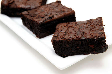 Sweet and tasty chocolate brownies served on a white rectangular plate against a light colored background