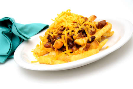 cheddar cheese: Melting cheddar cheese over the top of french fries covered in spicy chili with meat and beans Stock Photo
