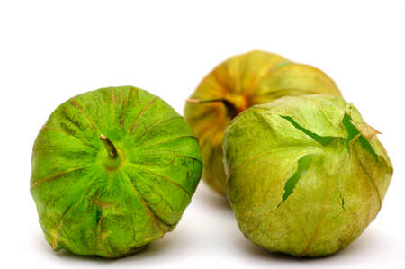 Three ripe tomatillos on a light colored background with various shades of green and brown on the husk ready to be peeled and used as the main ingredient for Mexican salsa verde.
