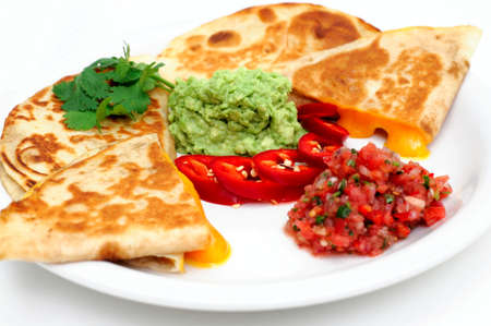 Cheddar cheese quesadillas with guacamole fresh salsa and sliced red chili pepper topped with guacamole and cilantro