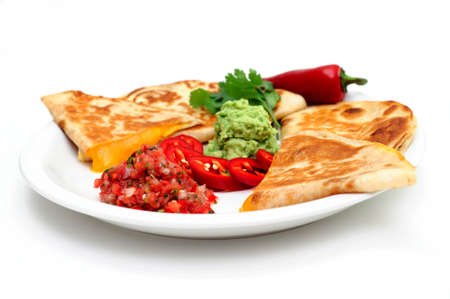 Cheddar cheese quesadilla's with guacamole fresh salsa and sliced red chili pepper topped with guacamole and cilantro