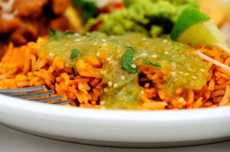 Spanish rice close-up with salsa verde made with tomatillo jalapeno garlic and cilantro poured over the top