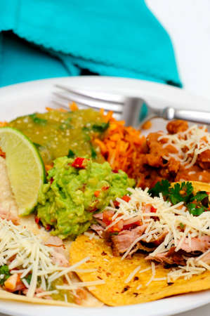 Mexican style meal of Pork Carnitas soft tacos with refried beans, Spanish rice topped with fresh salsa verde and spicy guacamole. photo