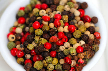 Peppercorns in various colors of red, green and the familiar black peppercorn on white in a small bowl