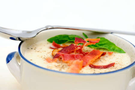 Potato soup topped with crisp bacon and fresh Basil leaves served in a rustic blue and white bowl