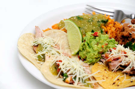 Mexican style meal of Pork Carnitas soft tacos with refried beans, Spanish rice topped with fresh salsa verde and spicy guacamole. Stock fotó