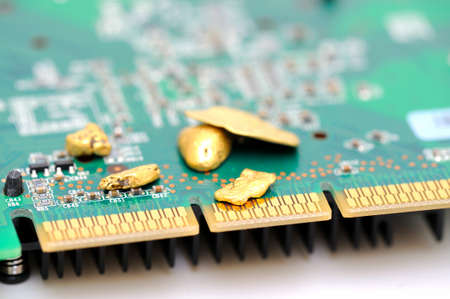 Gold is an important part of modern technology. raw gold nuggets on top of a finished circuit board  with gold plated connections