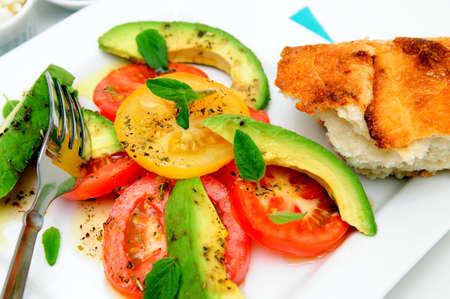 Tomates frescos de rojos y amarillos, rodajas de aguacate, hojas de albahaca y aderezo de vinagreta de frambuesa en un plato cuadrado blanco y un pedazo de pan artesano Foto de archivo - 8823005