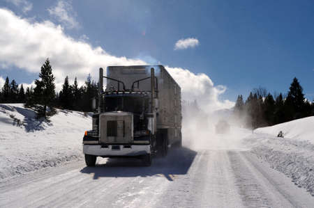 18: Big Rig and trailer driving down an icy and dangerous  road with snow blowing behind the truck on a cold clear day in the mountains