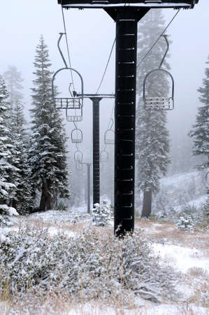Old ski lift pylons with cables and chairs disappear into a snow covered forest Imagens