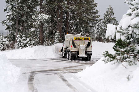 A large snow plow clearing a parking lot and road  in the forest