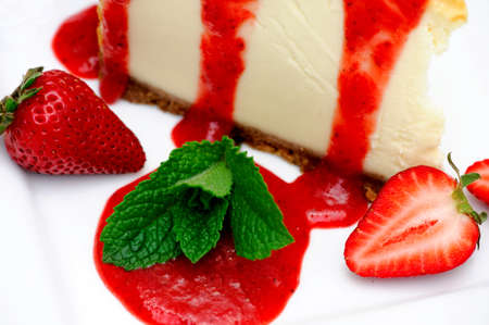 Fresh cheesecake with strawberry puree, whole strawberries and a sprig of mint leaves on a white plate